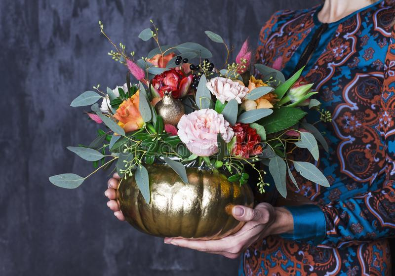 Jesień kwiecisty bukiet w pupkin wazie Kwiecista dekoracja w kobiecie obrazy royalty free