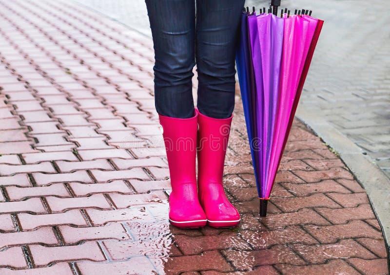 Jesień Ochrona w deszczu Kobieta (dziewczyna) jest ubranym różowych gumowych buty i kolorowego parasol zdjęcia royalty free