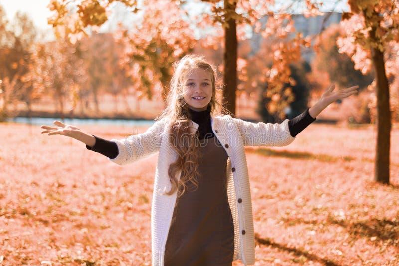 Jesień piękny portret młoda dziewczyna w parku z ulistnieniem nastolatek ręki w górę i uśmiechy obrazy stock
