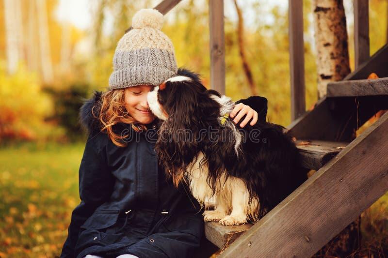 Jesień portret szczęśliwa dzieciak dziewczyna bawić się z jej spaniela psem w ogródzie obrazy royalty free