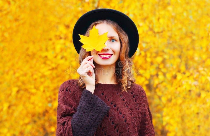 Jesień portreta uśmiechnięta kobieta chuje jej oko klonowych żółtych liście obrazy stock
