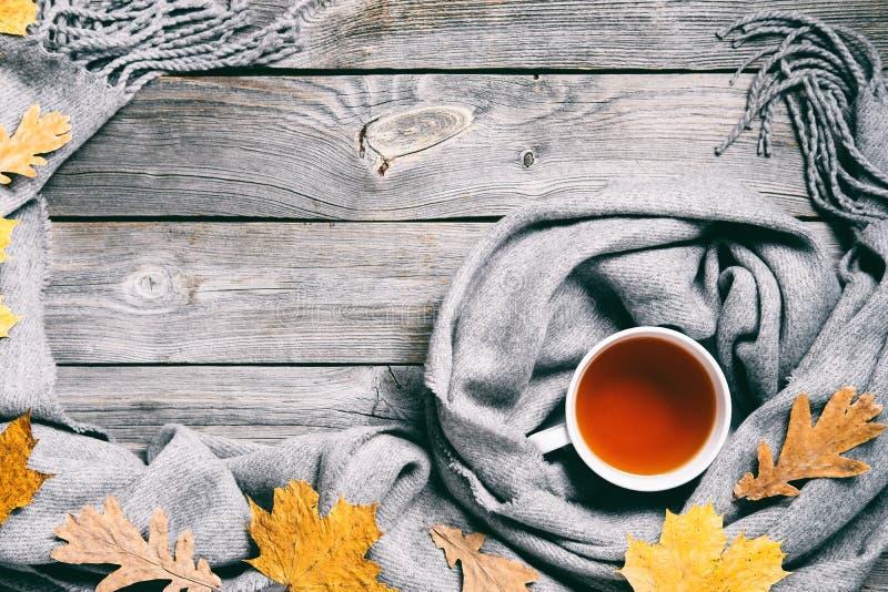 Jesień skład, spadków liście, gorąca parująca filiżanka herbata i ciepły szalik na drewnianym stołowym tle, Retro tonowanie fotografia royalty free