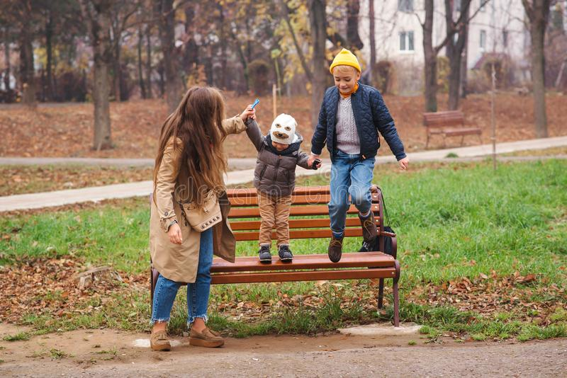 Jesienią szczęśliwa rodzina o naturze Matka i jej synowie dobrze się bawią na zewnątrz Jesienne święta Młody rodzinny spacer w je zdjęcia royalty free
