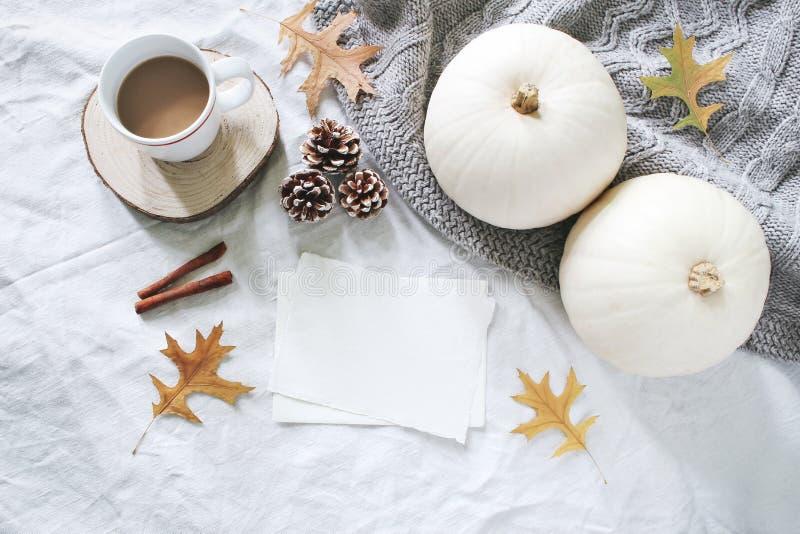 Jesieni śniadanie w łóżkowym składzie Pustych kart mockup Filiżanka kawy, białe banie, pulower, dębów liście i sosna, obrazy stock