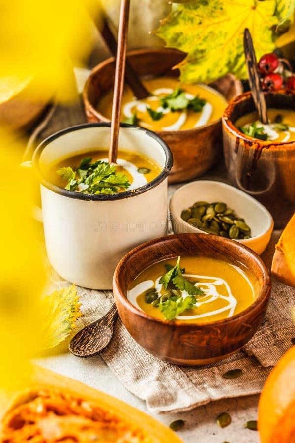Jesieni bani zupny puree z ?mietank? w fili?ankach jesieni sceneria Zdrowy weganinu jedzenia poj?cie fotografia royalty free