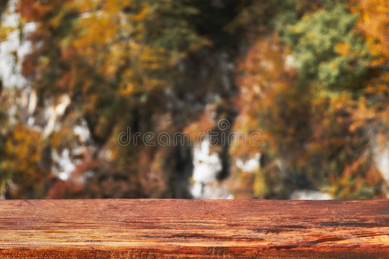 Jesieni bokeh tło z drewnianą deską w ostrości Zamazana spadek natura z brązu stołem obraz royalty free