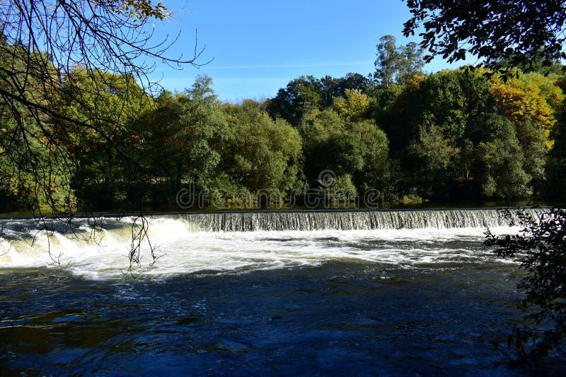 Jesieni colours w lasowych drzewach rzece z siklawą i Słoneczny dzień, niebieskie niebo, słońca światło z cieniami Galicia, Hiszp zdjęcie royalty free