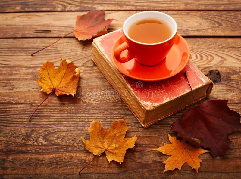 Jesieni liście, książka i filiżanka herbata na drewnianym stole, fotografia royalty free