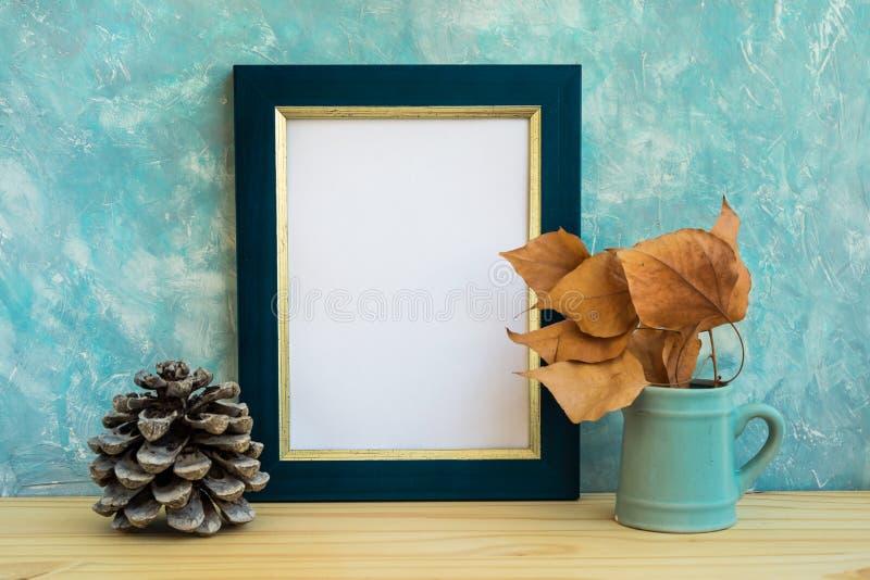 Jesieni mockup, błękitnej i złotej granica ramowa, gałąź z suchymi liśćmi w smołach, sosna rożek, betonowej ściany tło, wieśniak obrazy royalty free