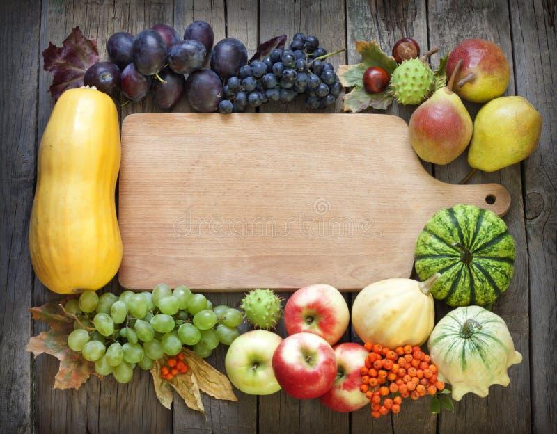 Jesieni owoc i warzywo i pusta tnąca deska zdjęcie royalty free