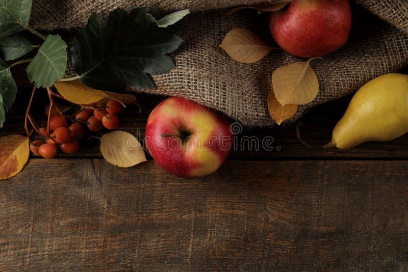 Jesieni przygotowania z owocowymi jabłkami, bonkrety i żółci jesień liście na brown drewnianym stole z miejscem dla inskrypci obraz royalty free