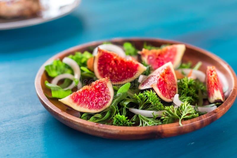 Jesieni sałatka arugula, figi w brown earthenware talerzu na błękitnym tle Odgórny widok obraz royalty free