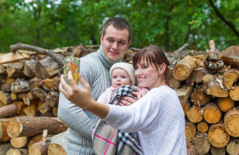 Jesieni scena Szczęśliwa młoda rodzina bierze selfie z smartphone w lesie zdjęcie stock