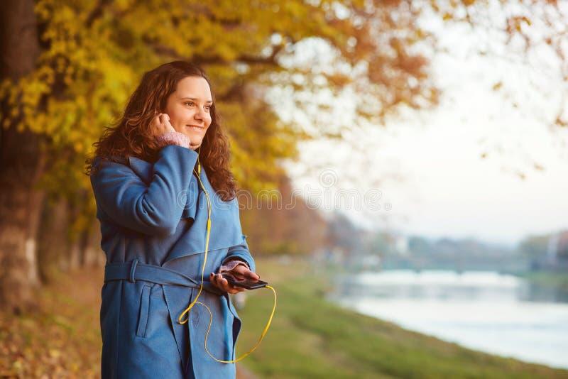 Jesieni styl życia mody portret młoda modniś kobieta outdoors Dziewczyny słuchająca muzyka outdoors w spadku czasie Piękna jesień obrazy stock