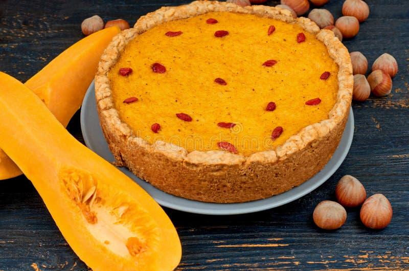 Jesieni tarta z goji jagodą dekorował z hazelnuts na czarnym nieociosanym drewnianym tle Tradycyjny deser dla dziękczynienia zdjęcia royalty free