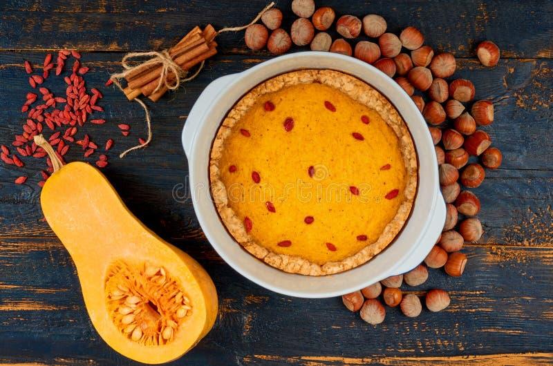 Jesieni tarta z goji jagodą w wypiekowym naczyniu dekorował z hazelnuts i cynamonem na czarnym drewnianym tle obraz stock