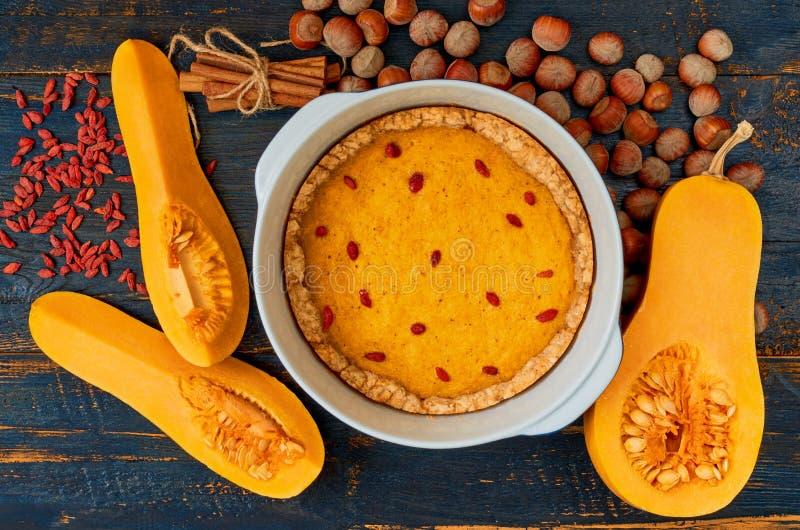 Jesieni tarta z goji jagodą w wypiekowym naczyniu dekorował z hazelnuts i cynamonem na czarnym drewnianym tle obrazy royalty free