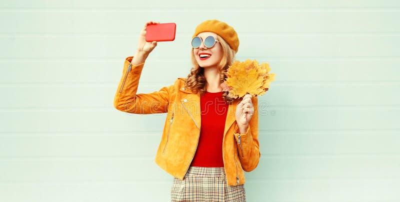 Jesieni uśmiechnięta kobieta bierze selfie obrazek telefonu mienia żółtymi liśćmi klonowymi jest ubranym francuskiego bereta kape zdjęcie royalty free