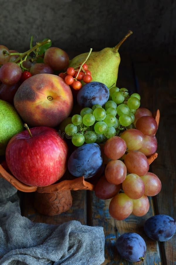 Jesieni wci?? ?ycie dla dzi?kczynienia z jesieni owoc i jagodami na drewnianym tle - winogrona, jab?ka, ?liwki, viburnum, dere? zdjęcia stock