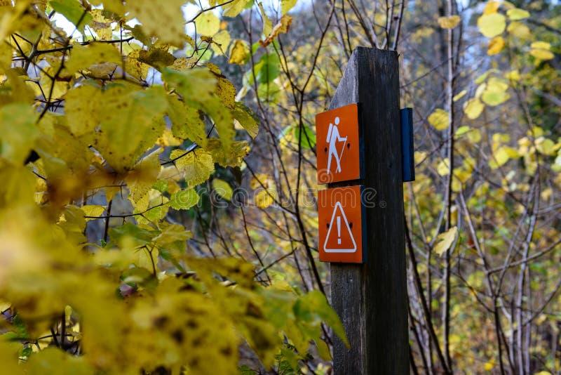 jesienie barwiący drzewa w parku z szyldowego ocechowania turystycznym śladem obraz stock