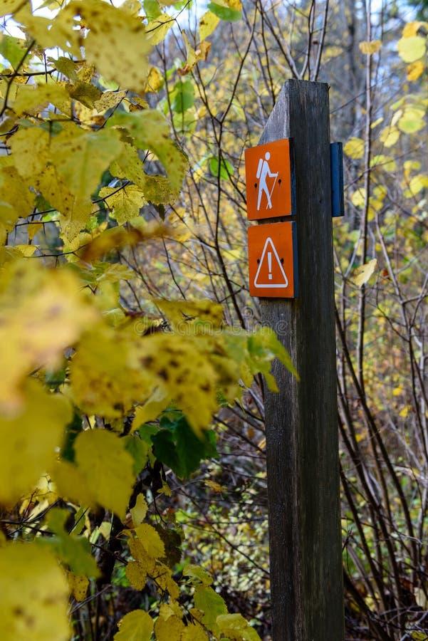 jesienie barwiący drzewa w parku z szyldowego ocechowania turystycznym śladem zdjęcie stock