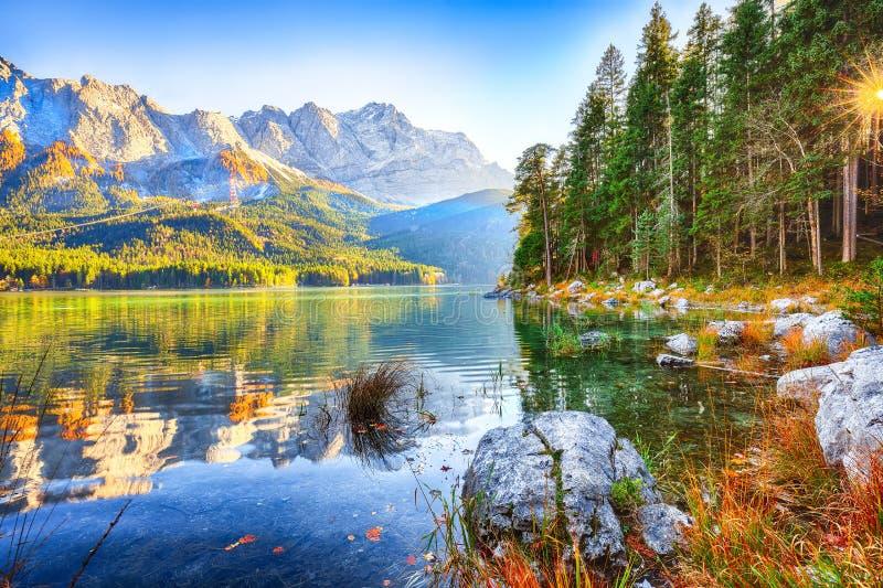 Jesienny krajobraz jeziora Eibsee przed szczytem Zugspitze pod słońcem zdjęcie royalty free