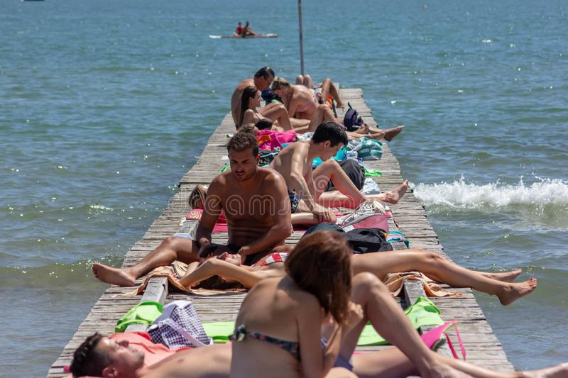 Jesolo, the beach as every year is filled, the sea once free, today is a captivating busines that can attract many tourists. Boys on a crowded dock sunbathing stock photography
