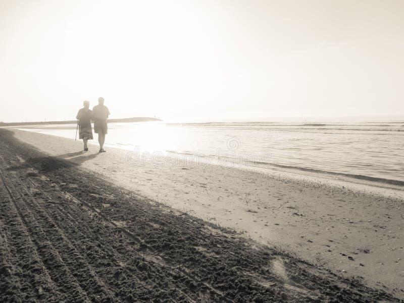 JESOLO, ITALIA - 27 DE AGOSTO DE 2017: dos envejecieron a la gente que caminaba al lado del otro largo la línea de la playa de un fotos de archivo libres de regalías