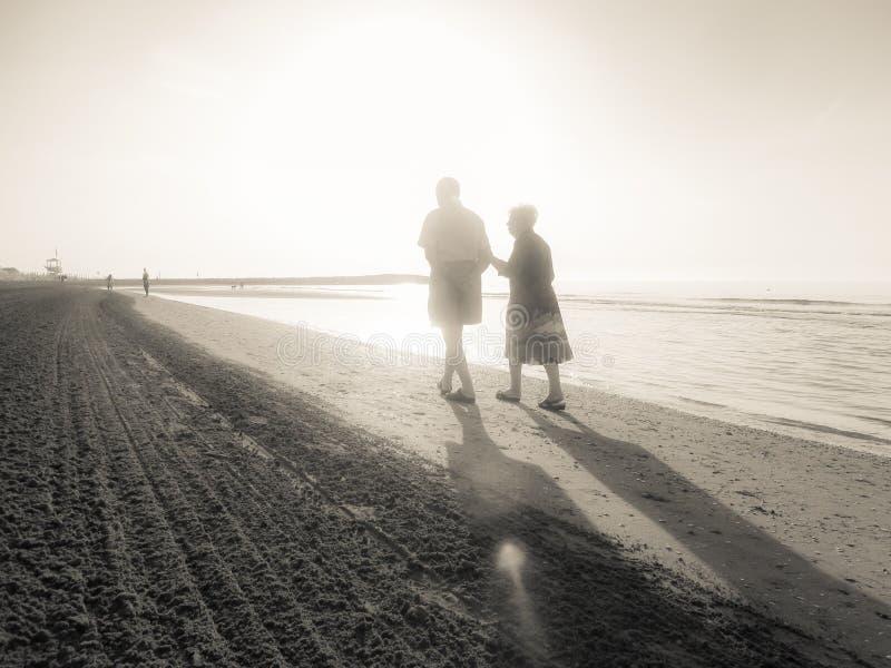 JESOLO, ITALIA - 27 DE AGOSTO DE 2017: dos envejecieron a la gente que caminaba al lado del otro largo la línea de la playa de un foto de archivo libre de regalías