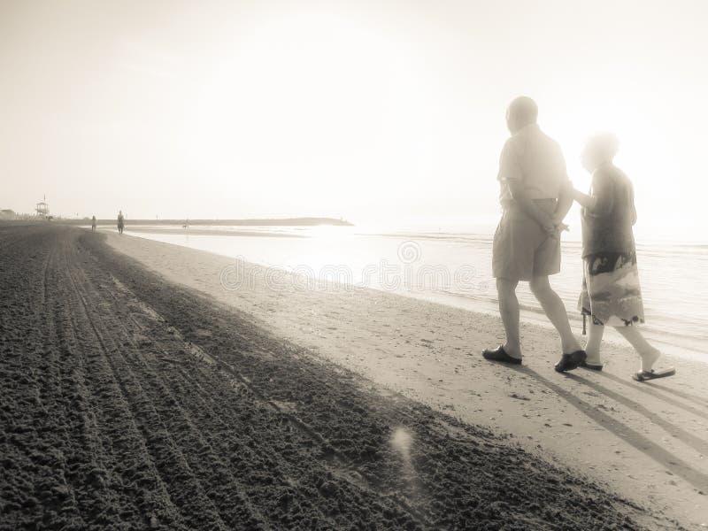 JESOLO, ITALIA - 27 DE AGOSTO DE 2017: dos envejecieron a la gente que caminaba al lado del otro largo la línea de la playa de un imagen de archivo libre de regalías