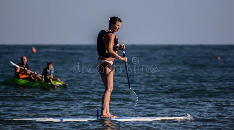 Jesolo strand, bilder, som beskriver turister, medan de tycker sig om med dragningar som skapas för havet, kanoter, självtabeller royaltyfri bild