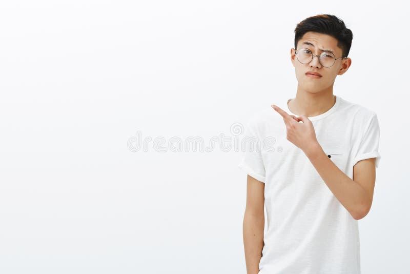 Jest ja wszystko ty dostać Portret nieporuszony wątpliwy młody mądrze azjatykci facet wskazuje z lewej strony w szkłach i białej  zdjęcia stock