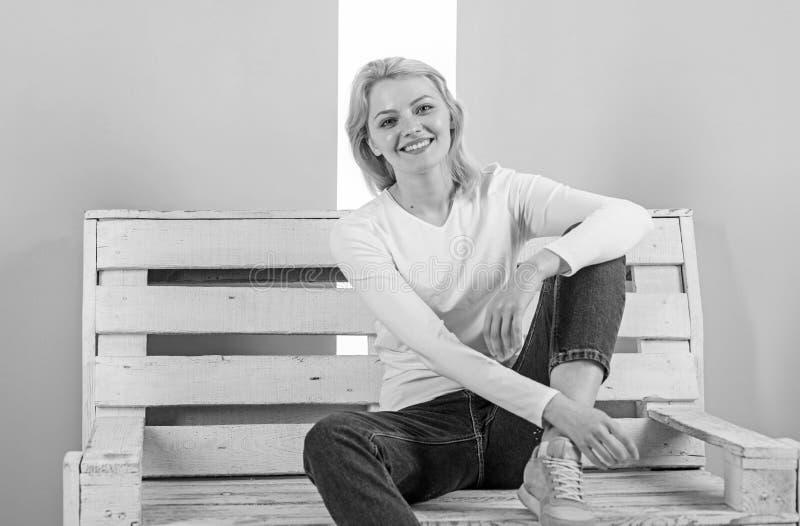 Jest po prostu wspaniała Piękny młoda kobieta uśmiech podczas gdy siedzący na ławce przeciw różowemu tłu Dziewczyna woli zdjęcie royalty free