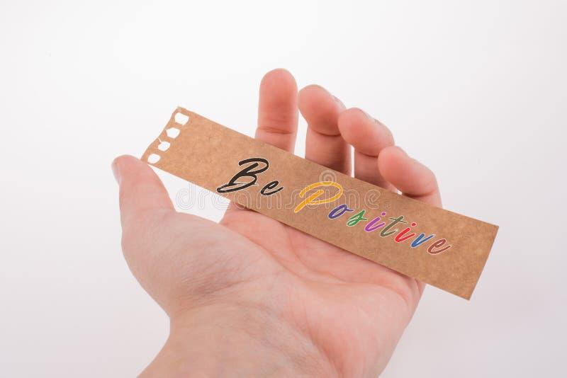 Jest pozytywnym wyceny literowaniem na poszarpanym notepaper w ręce zdjęcie stock