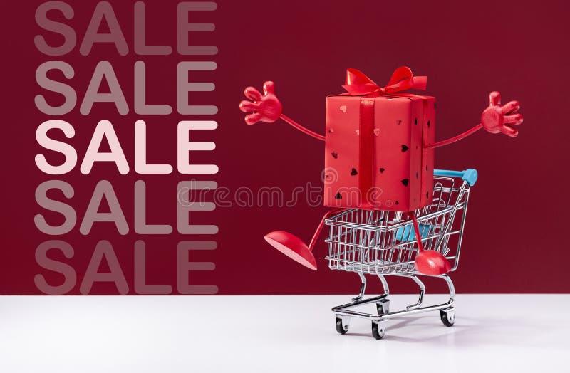 Jestem twój prezentem! Wózek na zakupy z niespodzianką w czerwonym świątecznym pudełku z nogami i rękami obraz royalty free