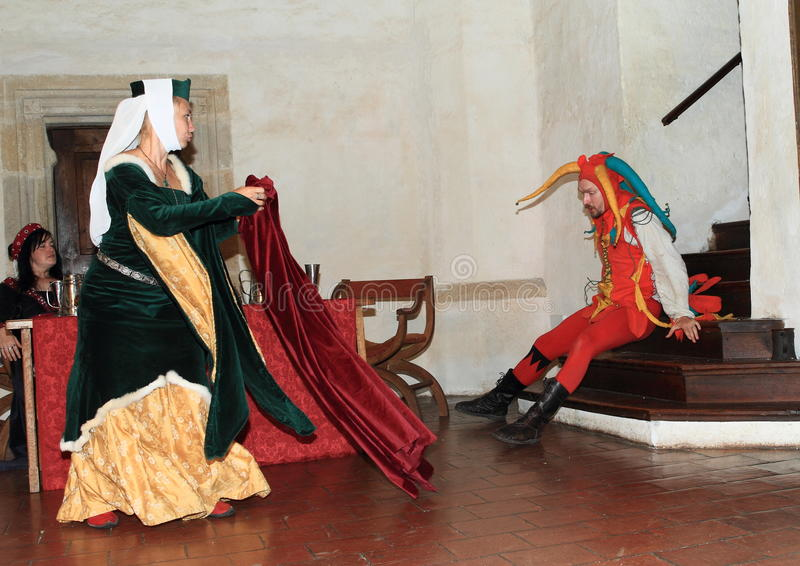 Jester falling down on bottom from stairs. Jester in colorful costume falling down on bottom from stairs while noble woman playing with coat like a Spanish stock image
