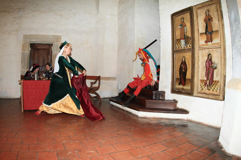 Jester falling down on bottom from stairs. Jester in colorful costume falling down on bottom from stairs while noble woman playing with coat like a Spanish stock images