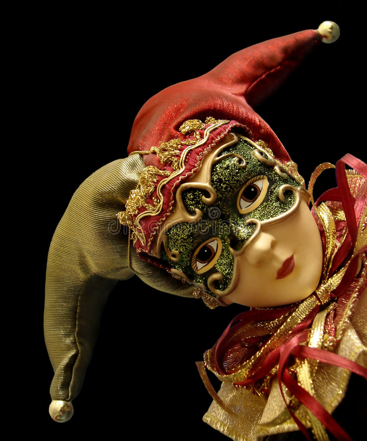 Jester with mask. Head of female Jester toy wearing mask and a red and green hat with bells isolated on black royalty free stock photo