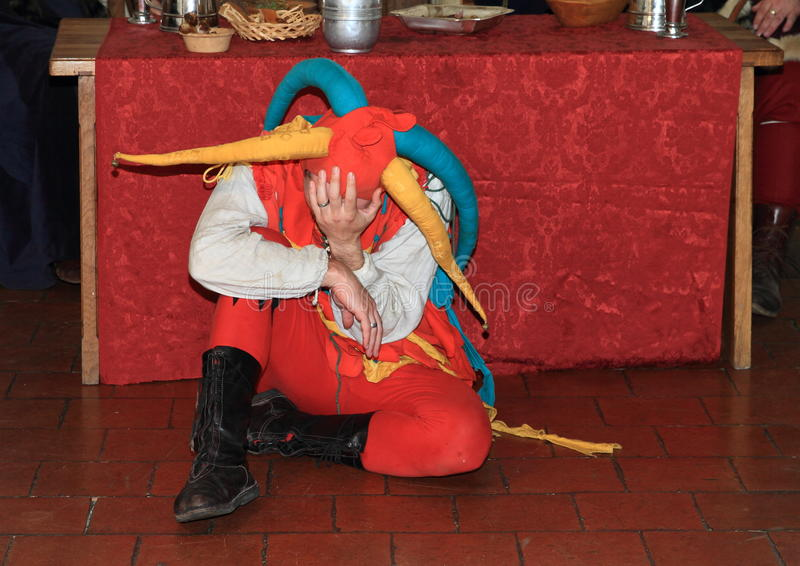 Jester sitting on floor. Jester in colorful costume sitting on floor by the table in banquet hall during Night performance A dozen small kegs or Cases of dead royalty free stock photos