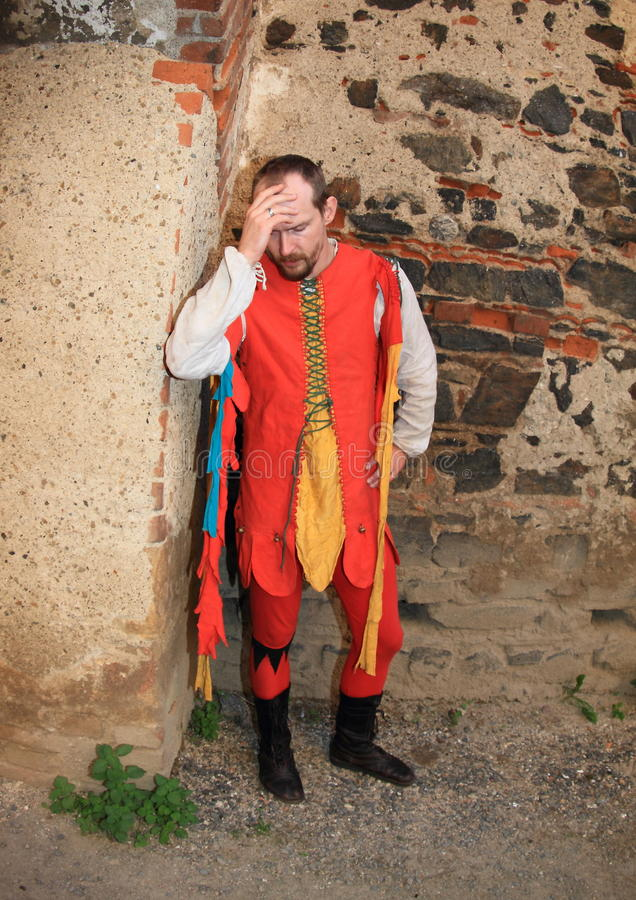Jester by wall. Jester in colorful costume standing by stone wall during Night performance A dozen small kegs or Cases of dead burgrave on castle Svihov (Czech stock photography