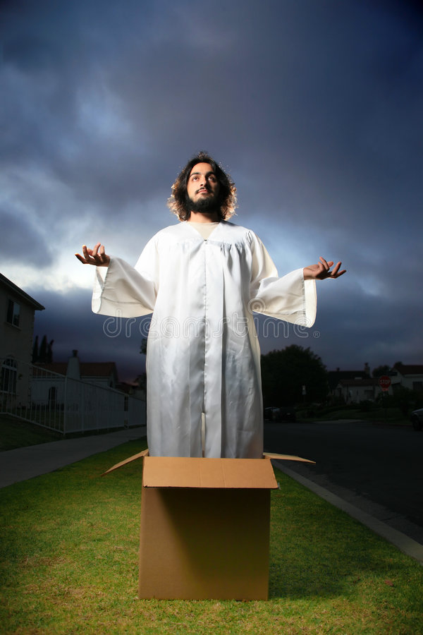 Jesus. Man looking like Jesus standing in the box with hands raised royalty free stock photo
