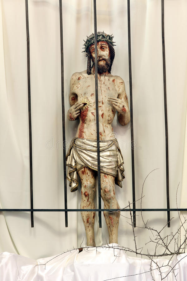 Jesus behind bars in prison. Wooden figure of Jesus in the church during Easter. royalty free stock photo