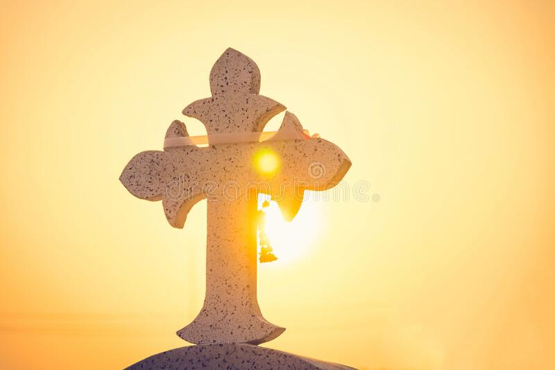 Jesus Christ cross. The Crucifixion, Resurrection and Easter concept. The Christian cross with a sunset scene in warm tone. Background with copy space stock photography