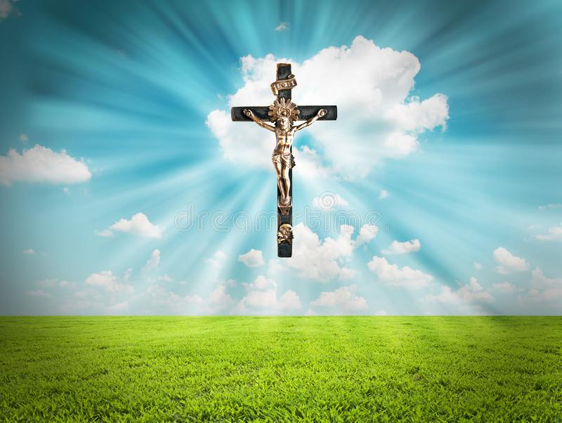 Jesus Christ on cross radiates light in sky over landscape stock image