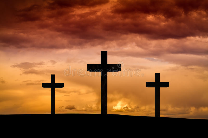 Jesus Christ cross on a red, orange sky with dramatic clouds, dark sunset stock photography