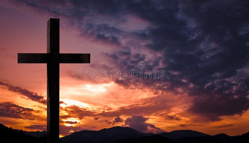 Jesus Christ cross, wooden crucifix on a heavenly background with dramatic light and clouds and colorful orange sunset stock photography