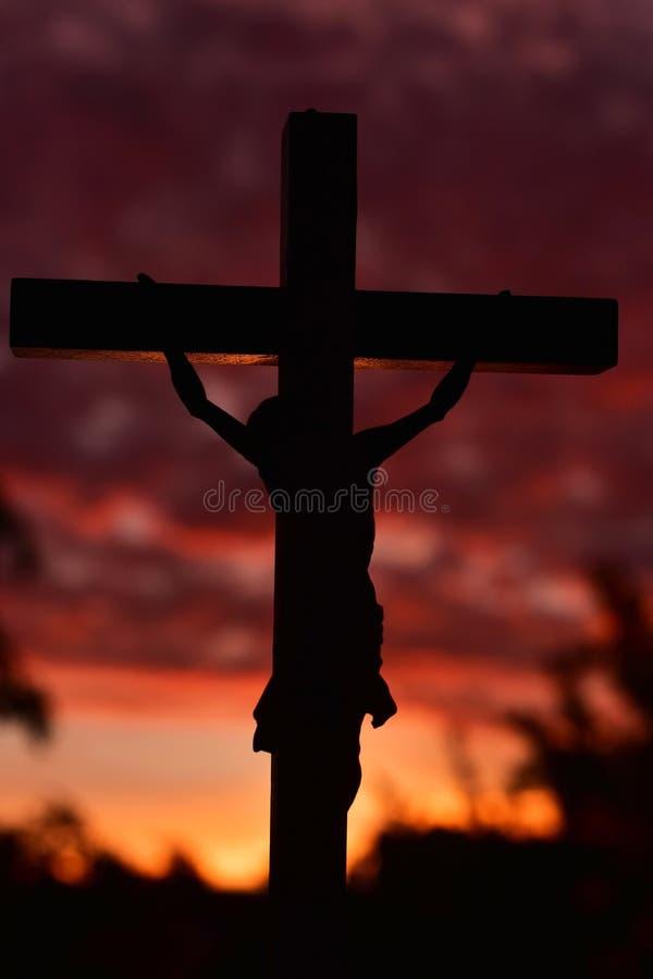 Jesus Christ cruza encima el cielo oscuro de la puesta del sol fotografía de archivo