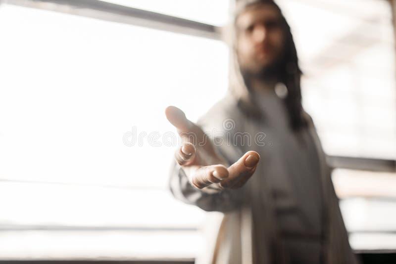 Jesus Christ in der weißen Robe, die heraus seine Hand erreicht lizenzfreie stockfotos