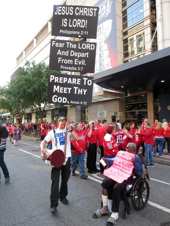 Jesus Christ and Homeless Veteran. Photo of man carrying a religion poster and homeless veteran in front of the capital one arena in downtown washington dc on 6/ stock photos
