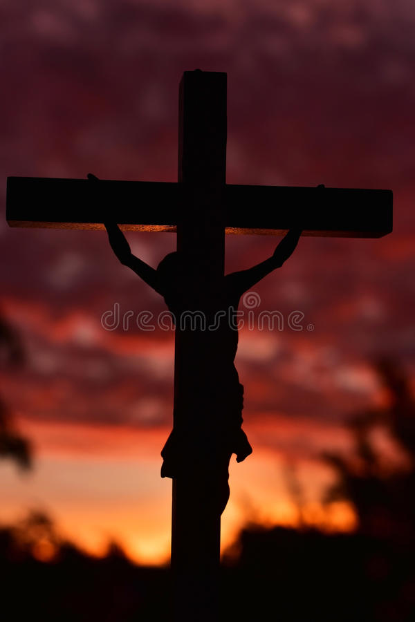 Jesus Christ korsar över mörk solnedgånghimmel arkivbild